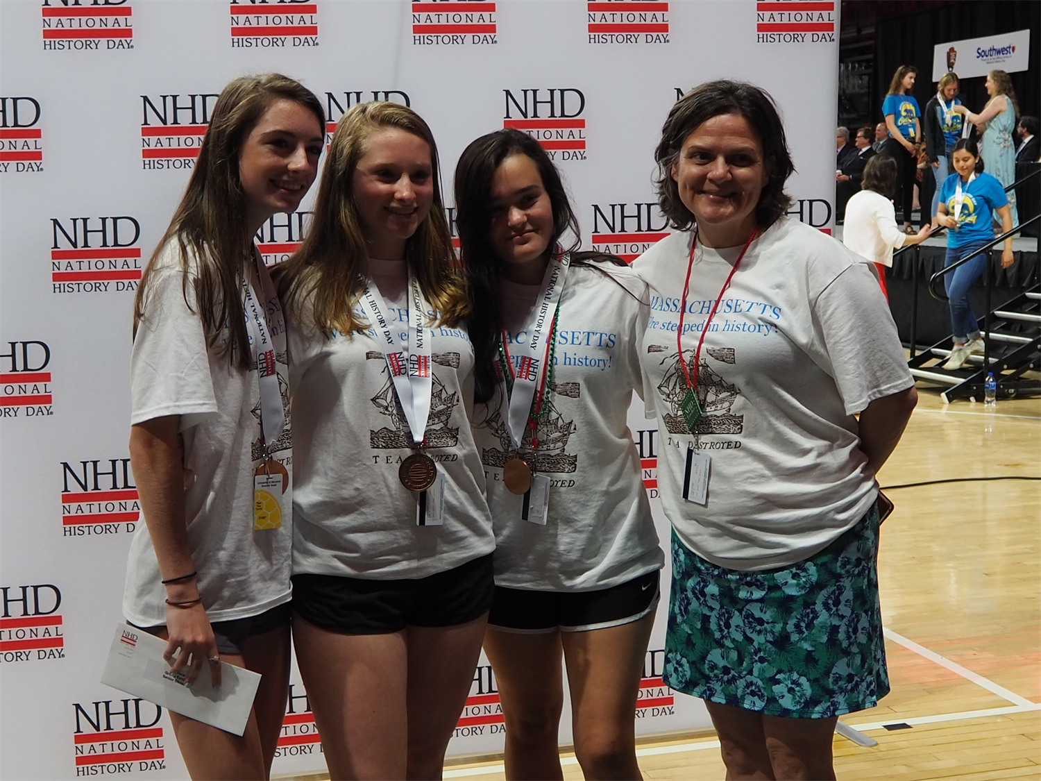 A teacher poses with three students in front of a backdrop with the NHD logo at the NHD National Competition.  All three students wear medals, and they and their teacher are wearing NHD Massachusetts T-shirts.