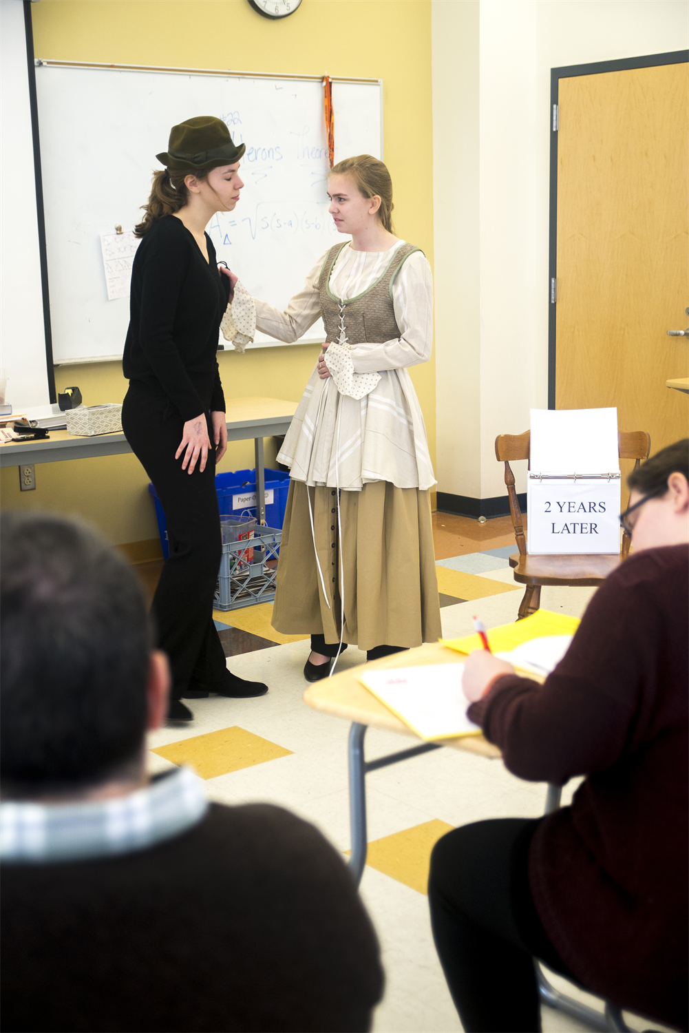 Two students perform a skit at the front of a school classroom while two judges watch and take notes.  One student is wearing all black and a cap with a rounded top, while the other wears an old-fashioned lace-up dress and an apron.