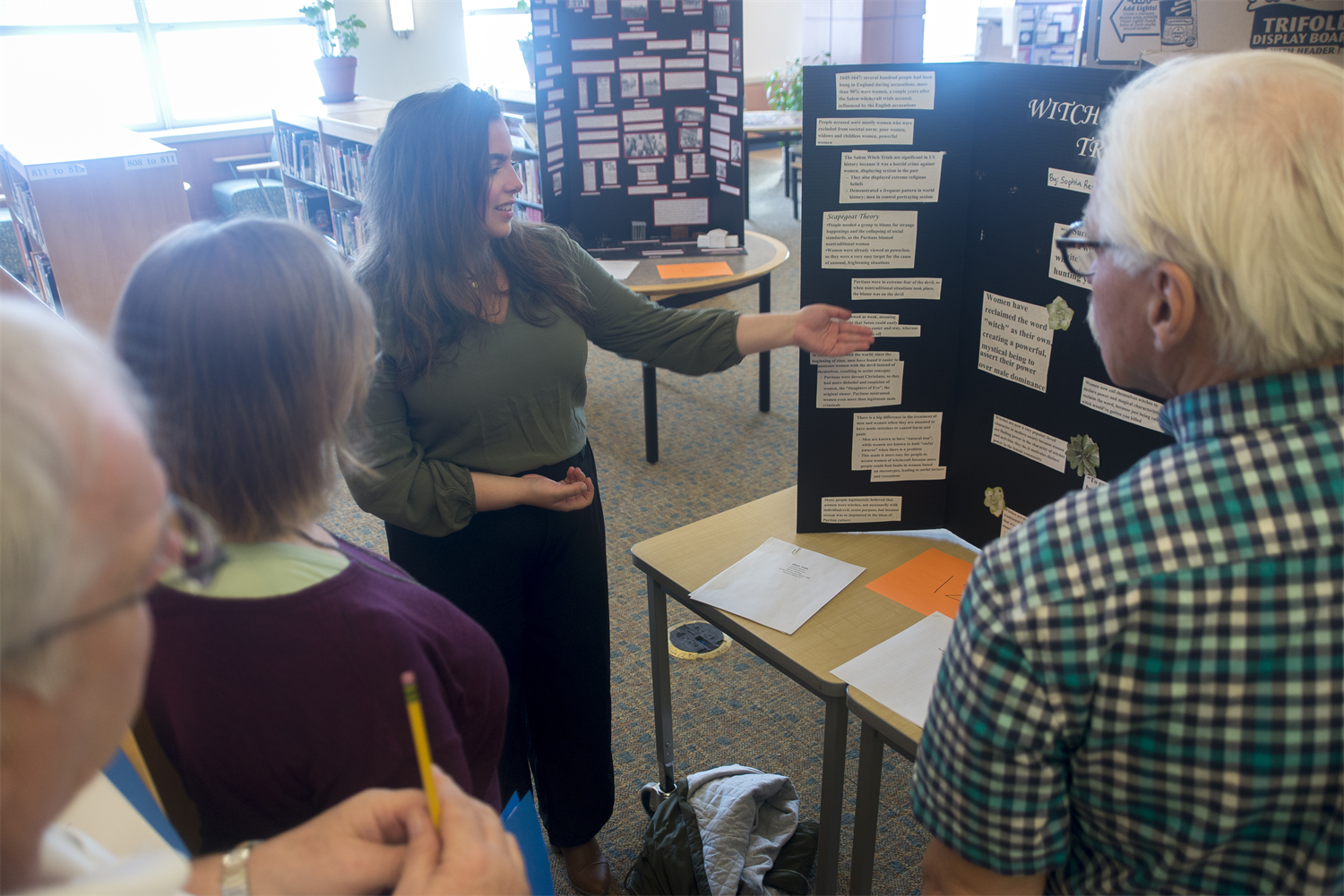 A student gestures toward an exhibit board, presenting their project to three adult judges.